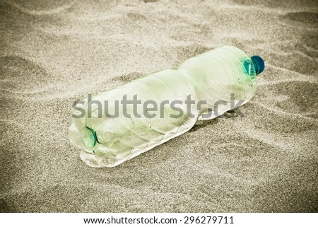 Empty bottle green plastic abandoned on the beach
