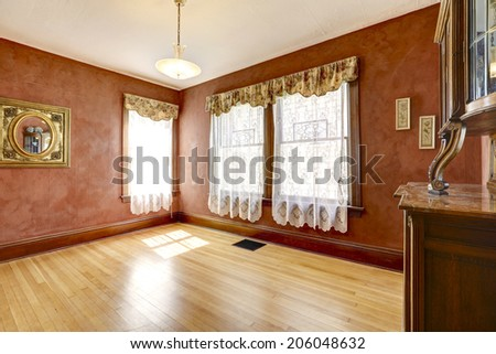 Empty bright red room with curtains and antique cabinet