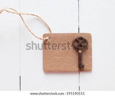 Empty brown cardboard tag on rough rope and rusty antique key on a white wooden board