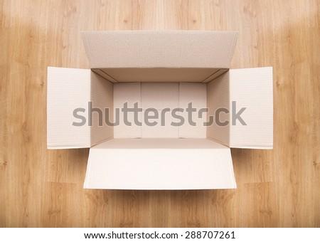 Empty brown carton box on the wooden floor