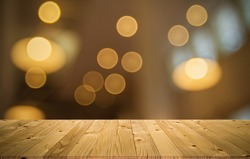 Empty brown old plank wooden board mock up display shelf with abstract beautiful blurred low angle view warming light bokeh from electric lamp and window lighting in coffee shop background.