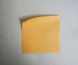 Empty brown sticker paper note isolated on white with clipping path. craft Brown paper with rolled edge hang on textured wall