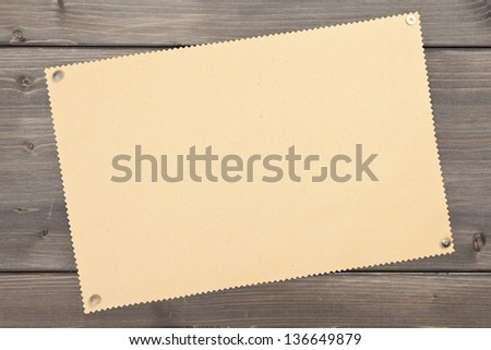 Empty brown vintage paper with pushpins on wooden background