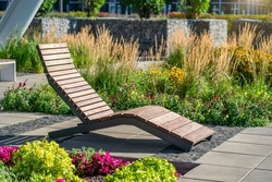 Empty brown wooden deck chair or chaise longue on tile among decorative grass and flowers in recreation area. Garden landscape with chairs in city park. Concept of recreation, tanning in yard