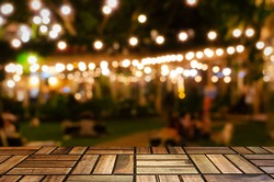 empty brown wooden floor or wooden terrace with abstract night light bokeh of night festival in garden, blurred background, copy space for display of product or object presentation, vintage color tone