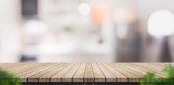 Empty brown wooden plank table top with blurred home kitchen with blur foreground leaf,Mock up template for display or montage of your design,Banner for advertise of product,panorama view