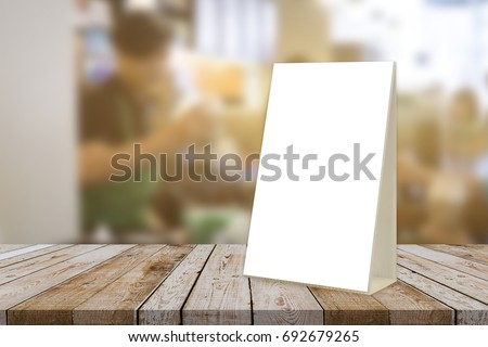 Empty brown wooden table and Coffee shop interior with Mock up Menu frame in Bar restaurant ,Stand for booklets with white sheets of paper acrylic tent card on cafeteria blurred background #692679265