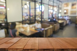 Empty brown wooden table and Coffee shop interior with some people meeting blur background with bokeh image,can be used for montage or display your products