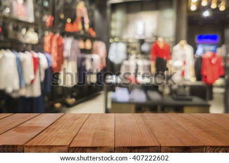 Empty brown wooden table and De focused/blurry background of Sports clothing store in Inter Sport store,with bokeh image, for product display montage,can be used for montage or display your products