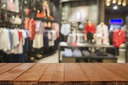 Empty brown wooden table and De focused/blurry background of Sports clothing store with bokeh image luxury and fashionable brand,can be used for montage or display your products