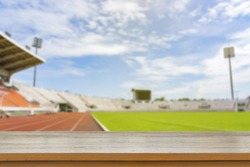 Empty brown wooden table top on blurred background of Red running tracks in sport stadium - can be used for display or montage your products