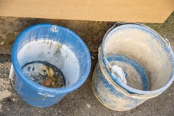 empty buckets with paint residues in blue and dirty