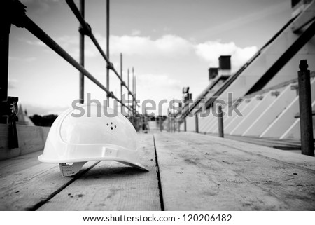 empty building site with left helmet on scaffold - stock photo