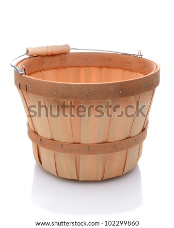 Empty bushel basket with a wood handle and stuffed with straw over a white background and slight reflection.