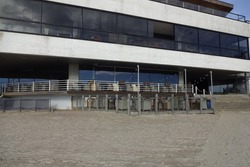 Empty cafe or restaurant on sand beach on a spring or summer day near a building with glass windows