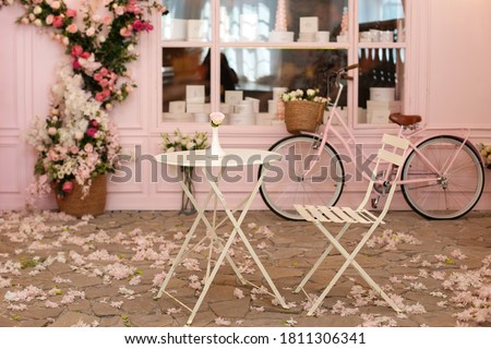 Empty cafe terrace with white table and chair. Pink exterior of the cafe restaurant. interior Street cafe. Cozy street with flowers and French-style cafe table. Decor facade of coffeehouse with bike.
