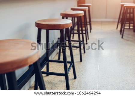 Empty cafe. Wooden chairs beside bar counter. Seats in row