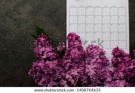 empty calendar with lilac flowers. flat lay pictures. dark wooden background