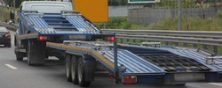 Empty car carrier truck with three-axle car transporter trailer drive on industrial area road, rear side wide view close up, delivery autos logistics, automobile transportation