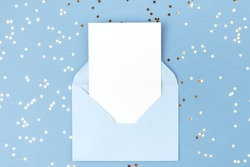 Empty card in blue envelope on blue background decorated with confetti. Holiday and invitation mockup.