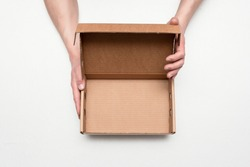 Empty cardboard box with copy space in the male hands on the gray background.