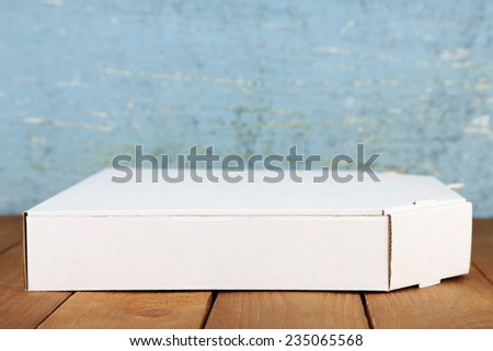 Empty cardboard pizza box on wooden table