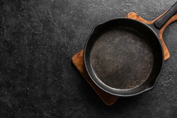 Empty cast iron frying pan for cooking on black background, top view, copy space. Cooking concept background with black pan.