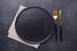 Empty ceramic plate, linen napkin and cutlery on dark stone background Copy space Top view - Image