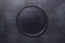 Empty ceramic plate on dark stone background Copy space Top view - Image