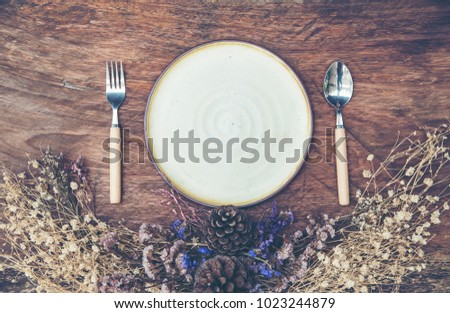 Empty ceramic plate with vintage flower on wooden background #1023244879
