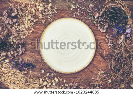 Empty ceramic plate with vintage flower on wooden background #1023244885