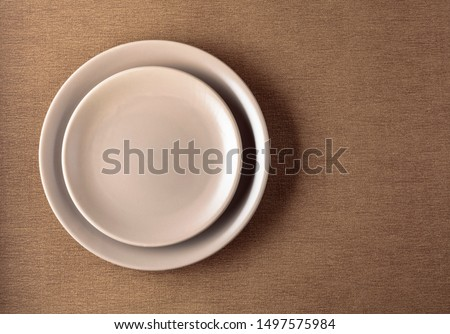 Empty ceramic round beige plate on a beige tablecloth. Copy space. #1497575984