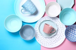 Empty ceramic tableware. Ceramic plates and cups on pink and blue background. Overview empty food table with tableware. Set of different modern white and blue plates,bowls and cups.Top view,flat lay