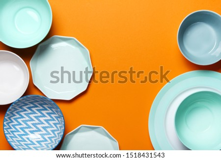 Empty ceramic tableware. Ceramic plates on orange background. Overview empty food table with tableware. Set of different modern white and blue plates and bowls.Top view, flat lay.Copy space for text