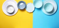 Empty ceramic tableware. Ceramic plates on yellow and blue background. Overview empty food table with tableware. Set of different modern white and blue plates and bowls.Top view, flat lay.Copy space.