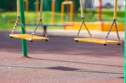 Empty chain swings on summer kids playground