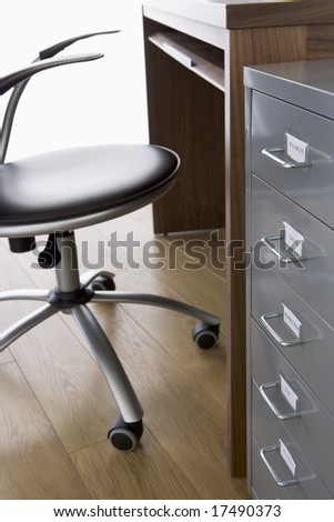 Empty Chair And Desk With Filing Cabinet