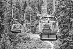 Empty chair lift in a mountain summer scenario.