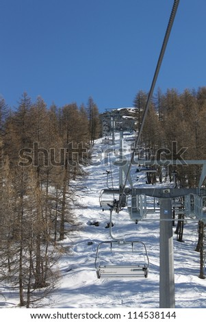 Empty Chair Lift in the mountain with casted larch astride