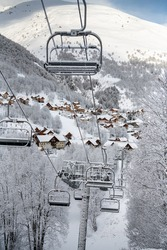 empty chair lifts in a Swiss ski resort closing up because of corona virus. The last skiers are on the slope. The resort is more or less abandoned due to official ban of ski resorts operation