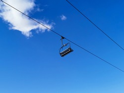 Empty chairlift with a blue sky