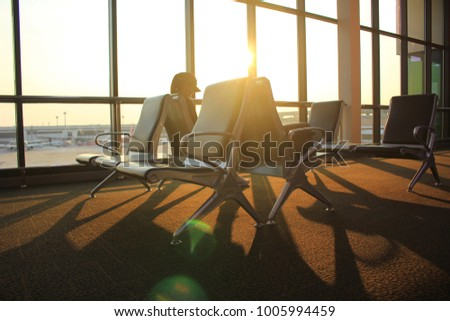 Empty chairs and passenger in the airport terminal on evening sunset light #1005994459