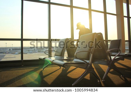 Empty chairs and passenger in the airport terminal on evening sunset light #1005994834