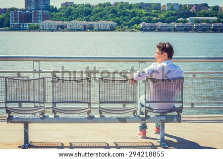 Empty Chairs for You. lonely man seeking friendship. Wearing white shirt, jeans, sneakers, a young lonely guy sitting by Hudson River in New York, facing New Jersey, waiting for you. Copy Space.
