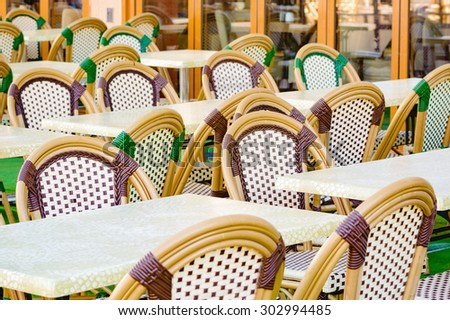 Empty chairs from outdoor diner before the customers arrive. Woven material in purple and green on chairs.