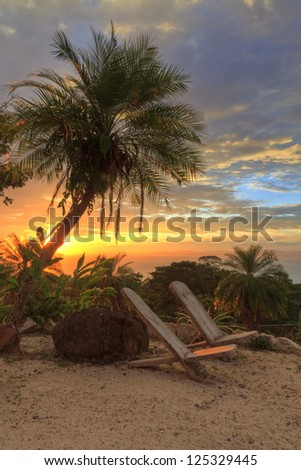 Empty chairs under a plam tree on a poolside 'beach' overlooking the Pacific Ocean and Nicoya Peninsula at sunset near Tarcoles, Costa Rica (HDR)