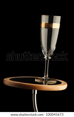 empty champagne glass with golden details on makeup mirror - stock photo