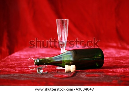 empty champagne glasses and bottle lay on wet red velvet after the party