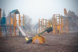 Empty children's playground on a foggy autumn morning.