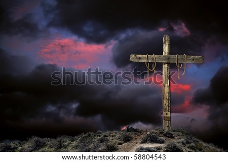 Empty Christian cross against angry cloudy sky representing the immediate aftermath of the crucifixion of Jesus Christ.